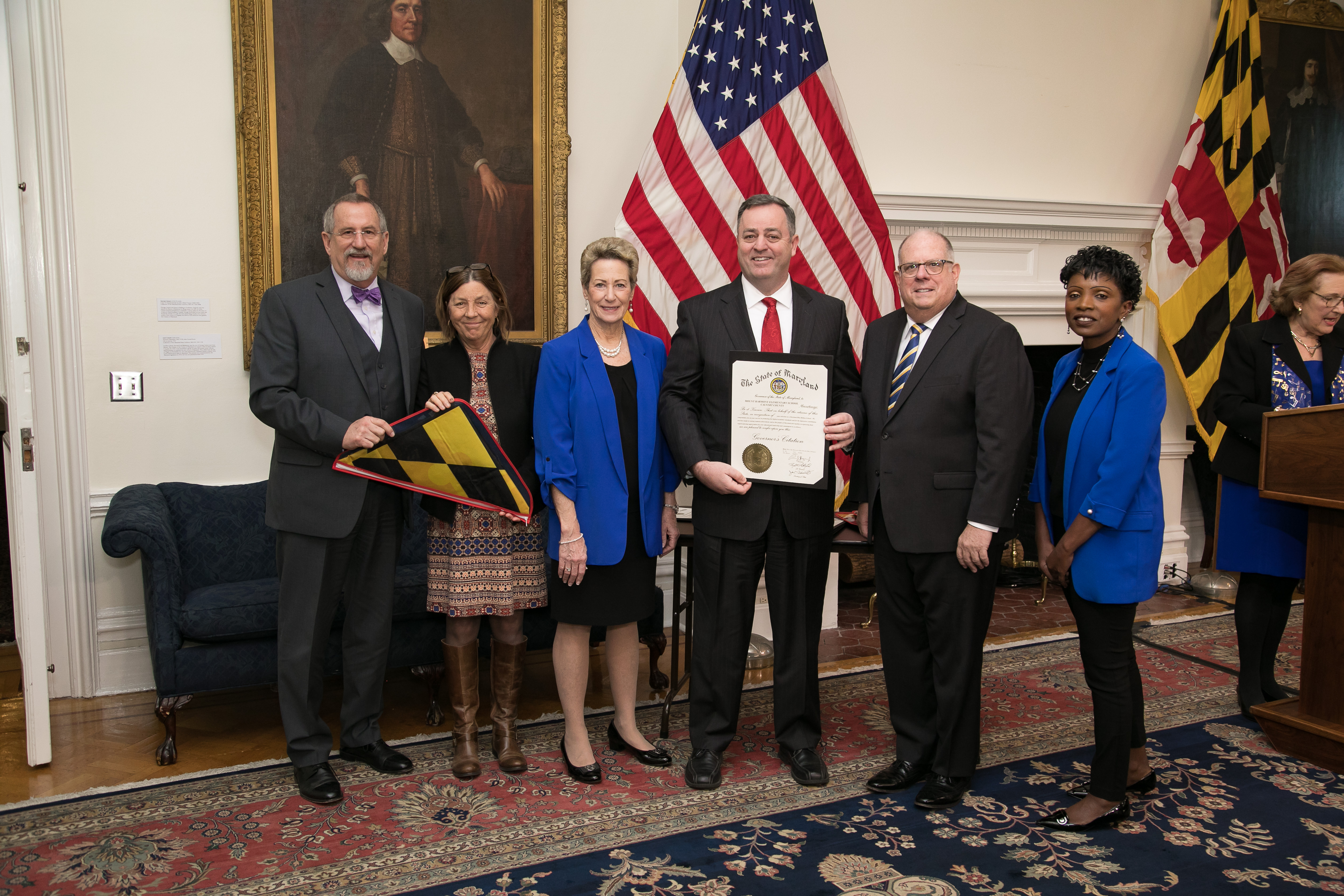 Maryland Governor Larry Hogan, State Superintendent of Schools Dr. Karen B. Salmon with 3 representatives from Mount Harmony Elementary School holding a certificate and a Maryland flag.