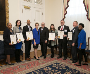 6 people holding certificates stand with Maryland Governor Larry Hogan and Maryland State Superintendent of Schools Dr. Karen B. Salmon