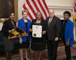 Maryland Governor Larry Hogan, State Superintendent of Schools Dr. Karen B. Salmon with 3 representatives from Glenarden Woods Elementary School holding a certificate and a Maryland flag.