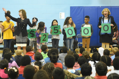 At an elementary school assembly in the gym, students and faculty hold up signs that spell out $25,000