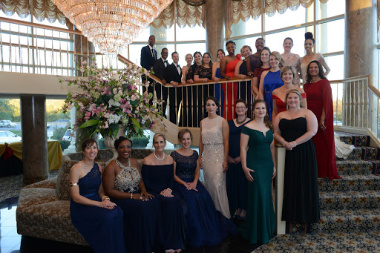 Maryland Teacher of the Year finalists wearing formal wear gather under a chandelier