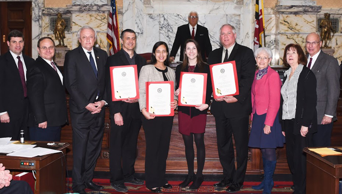 2 men and 2 women holding certificates pose with State legislators in the front of the Maryland General Assembly