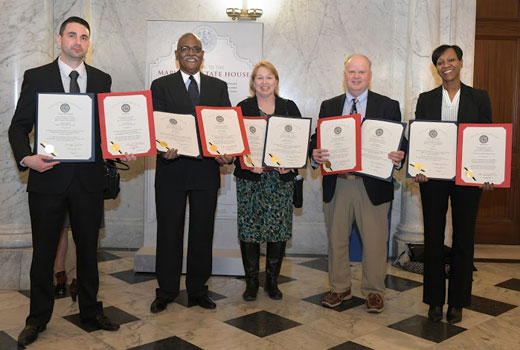 Three men and two women hold certificates in the hallway of the Maryland State House.