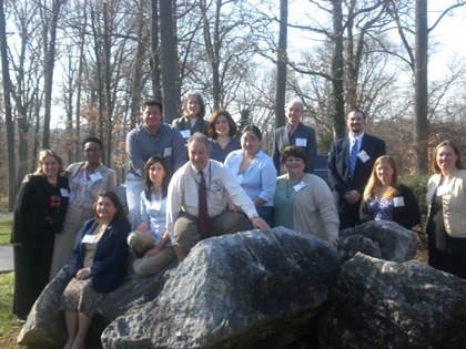 A group of service-learning fellows posing around a large rock formation at a Fellows Training Event